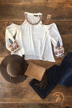- Embroidered cold shoulder top - Retro earth tone floral embroidered details at neckline and cuffs - Keyhole font detail - Back keyhole with hook and eye closure - Flattering curved hem with slightly