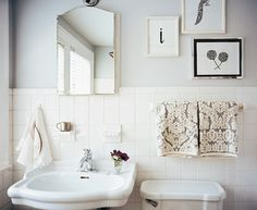Beautiful vintage bathroom design with soft gray walls paint color, white pedestal sink, white porcelain tiles backsplash and white & gray damask hand towels.