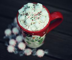 hot cocoa with whipped cream, marshmallows and christmas sprinkles in christmas mug