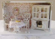 Quadro em mdf pintado com tinta pva, mobiliário em madeira e peças em resina pintadas a mão. Fundo forrado com tecido 100% algodão. As peças deste produto podem sofrer alterações de acordo com o estoque da loja, tais como bules, xícaras e pães. R$ 160,00