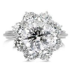 In a breathtaking Retro-era design, a spectacular center diamond is encompassed by eight round brilliant cut diamond accents. Scroll detailing in the shoulders complete this antique beauty (approx. 3.36 total carat weight).