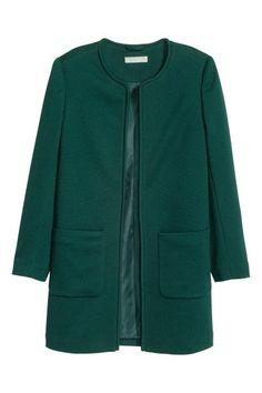 Krótki płaszcz: Krótki płaszcz ze strukturalnej tkaniny. Długi rękaw, bez zapięcia, naszyte kieszenie. Z podszewką.