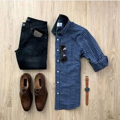 Men's dark denim, blue checker button down shirt, and brown leather shoes.