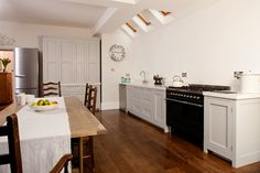 Wooden kitchen with light grey units and white corian top