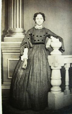 Interesting sleeves and collar. The bodice is either extremely well matched and smoothly fastened in the front, or it is back-fastening. She appears fairly young, and her hair maybe cropped and curled.