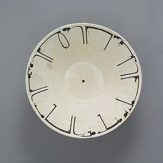 """The ornamental calligraphy on the rim of this 10th century Iranian bowl says """"Planning before work protects you from regret."""" The painter had to carefully plan the inscription to cover the entire rim evenly. He had a sense of humor about his work."""