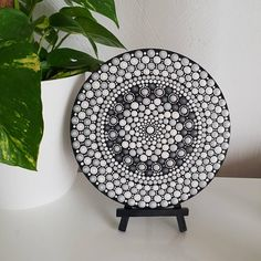 This hand-painted mandala dot art is created on a round 18cm wood slice from the French Riviera. It is painted all black, with detailing in a mix of grey, silver and white finished with a lighter shade of each colour in every dot. This art will brighten any home. It is a beautiful piece