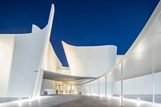 Fluted slabs of white concrete with a bush-hammered finish forms the walls of this museum, while a crescent-shaped pond wraps the building, intended to create a visual connection with the park.