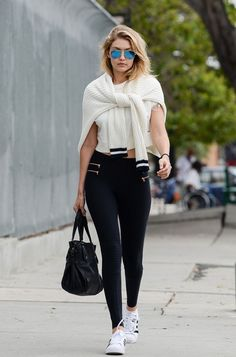 Gigi Hadid wears a cropped t-shirt, sweater, leggings, Adidas sneakers, mirrored sunglasses, and a tote bag