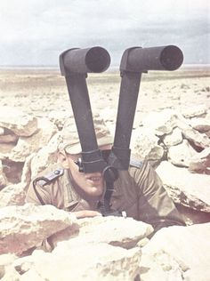 """An AfrikaKorps lieutenant scopes the enemy with his """"scissor glasses"""". German made scissor glasses had a reputation for superior optics and field endurance. A must for artillery observers and tactical battlefield diagram drafters."""