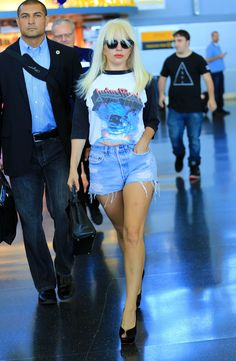 Lady Gaga wears a Judas Priest concert t-shirt, shredded denim shorts, and peep-toe stilettos