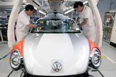 Employees place a windshield on a Volkswagen AG Beetle at the company's assembly plant in Puebla, Mexico