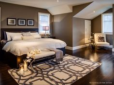 A warm and cozy bedroom with dark hardwood floors and brown paint. The white…