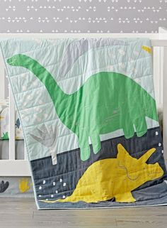 Shop Dinosaur Crib Bedding.  Our Dinosaur Crib Bedding includes a blue baby quilt with multicolor print and embroidered dinos.  The quilt is coordinated with a changing pad cover, crib skirt and crib fitted sheet that have multicolor dinosaur prints.