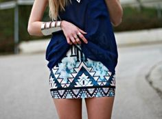 This blue and white aztec pencil skirt, and the big cuff on her arm, please.