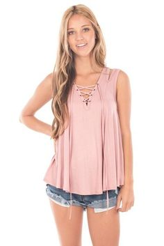 We've been dreaming of the Blush SleevelessLace-Up Top! Woven rayon falls into a roomybodice off of a cut out shoulder, lace-up neckline and tasseled ties. So