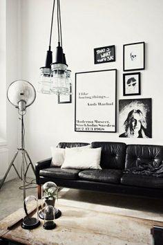 deco cocooning avec un canapé en cuir noir, peintures murales blanc-noir