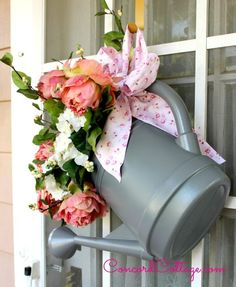 Hometalk   Watering Can Door Hanger...I added the roses, some faux hydgrangea I had and I grabbed my scrap fabric bag and cut a piece and made a bow for it.