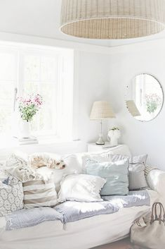white sofa, beach coastal cushions and colours, wicker pendant light