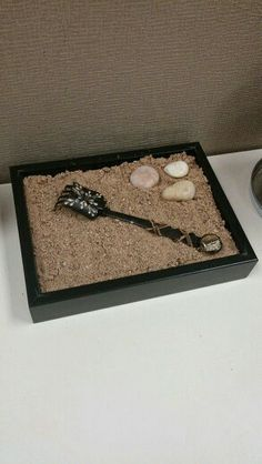 Diy zen garden. Make with an old picture frame,  and from a sandbox, and a fork with buttons and leather.  Duct tape the back of the frame together after taking out the glass.  Put in the sand with a few rocks.  Spray paint an old fork, hot glue buttons or rocks on the ends of it, and wrap with leather shoelaces.  Presto! Inexpensive and a great table top zen garden!