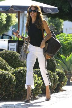 Dressed to impress: The 46-year-old looked chic in a pair of cropped white jeans, a black tank top, and sky-high heels