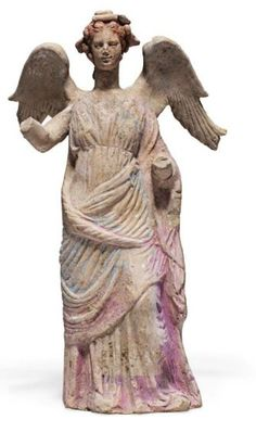 Canosan terracotta standing winged Nike, 3rd century B.C.   Standing with her right leg slightly advanced, wearing a chiton with himation wrapped across her body and draped across her left arm, her right arm raised, her hair gathered in a chignon at the nape of her neck and crowned with a foliate and berried wreath, remains of red, white, blue and pink pigment, 31.8 cm high. Private collection