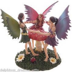 Lovely fairy figurine 3 fairies decorated with wild flowers dance around a toadstool on grass with flowers and a little ladybird at their feet