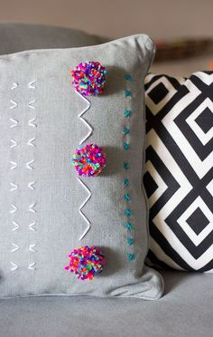 Accessorize your couch with an embroidered pom pom pillow using this home decor DIY project.