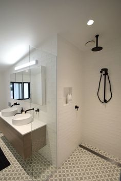 Modern white and grey bathroom with timber wall hung vanity, grey petal encaustic floor tiles, white handmade subway wall tiles and black tapware. See all the photos from this bathroom and find out where to source the products...