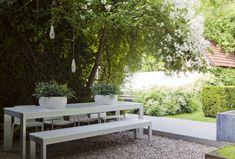 Terras van grint met witte tafel. bankje scheelt ruimte. Moderne stadstuin / denkers in tuinen