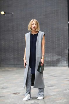 Rock a grey sleeveless coat with grey knit skinny pants for a standout ensemble. Dress down your look with white low top sneakers.  Shop this look for $330:  http://lookastic.com/women/looks/clutch-and-watch-and-low-top-sneakers-and-tunic-and-sleeveless-coat-and-pearl-necklace-and-skinny-pants/3741  — Dark Green Leather Clutch  — Gold Watch  — White Low Top Sneakers  — Navy Silk Tunic  — Grey Sleeveless Coat  — White Pearl Necklace  — Grey Knit Skinny Pants