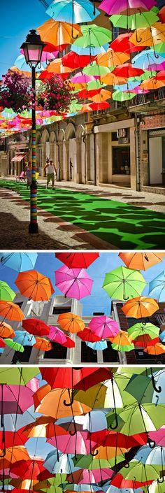 A fotógrafa Patricia Almeida registrou essa bela instalação artística nas ruas de Portugal feita com guarda-chuvas coloridos formando um teto no meio da rua.
