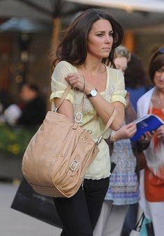 Duchess Catherine in pale yellow top, black pants, and caramel-colored handbag