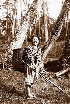 Smiling country girl raking leaves. Old Japan.