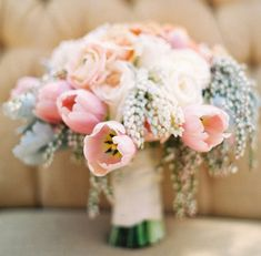 Totally romantic. Pale-pink tulip bouquet with pieris, dusty miller leaves, and ranunculuses.