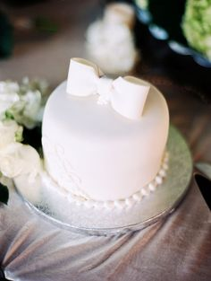 simple white cake tied with a bow #whitecake #weddingcake #cleandesign