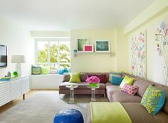 Contemporary family room and playroom combo features walls painted pale yellow lined with art over a milk brown sectional lined with chartreuse and turquoise blue pillows alongside a blue Moroccan leather pouf and a pair of acrylic side tables facing a white rippled media cabinet placed under a flat panel tv.