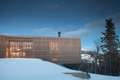 Pine louvres cover the glazed sides of this cabin by Lund Hagem, which forks at one end to present two large windows towards slopes at a ski resort.
