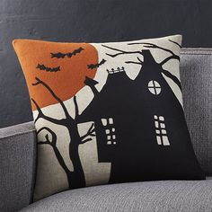 A haunted house with bats silhouettes black against an orange moon on this spooky Halloween-themed pillow. Felt appliqué and interlocking embroidery stitches add dimension to the pillow's graphic design. Pillow reverses to solid natural cotton.