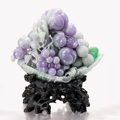 LAVENDER JADEITE AND JADEITE 'PROSPERITY' CARVING Of celadon tone suffused with intense lavender and patches of apple green, carved as a basket of fruits including peaches, grapes, finger citron and lychees, and a ruyi on one end, symbolising prosperity and abundance.