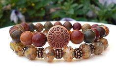 Earthy stacked bracelets are made with gorgeous 8mm Picasso Czech rondelles that…