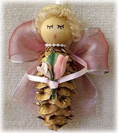 "Small Pine Cone Angel Ornament - Wire Ribbon Wings.  The Small Angels are made from Douglas Fir or Spruce cones and are around 3"" to 4"" tall.  The cone is spray painted gold.  Wings are wire edged ribbon.  Ribbon colors include pink (pictured), copper/gold, cream, and gold.  Flowers held by the angel are cream or pink."