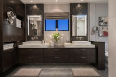 Chocolate-brown cabinetry fills this contemporary bathroom, providing ample storage for the spacious neutral room. The mosaic tile backsplash, long double vanity and sleek white vessel sinks add chic sophistication to the space.