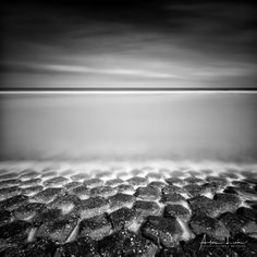 Layered - At the beach again, for some long exposure shots. Those were taken at Breskens, The Netherlands. I was close to the lighthouse of Breskens. The water was very high and calm. It reached the stoned structure that protects the dunes. I love the different kinds of structures and textures in this shot, and its well balanced composition. #BW #Breskens #beach #blackandwhite #blackandwhitephotography #coast #coastline #landscape #landscapephotography #long #exposure #longexposure…