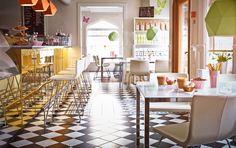 """Ein Café mit Eisdiele mit verchromten BERNHARD Stühlen mit Lederbezug """"Kavat"""" in Weiß und Tischen mit weißen Tischplatten aus Glas und verchromten Beinen"""