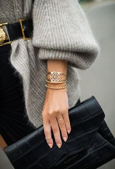 Grey cardigan, gold jewelry and a black clutch.