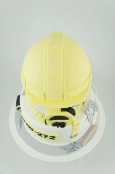 Hard Hat cake created by two little figs cakes. Grey white yellow silver fondant cake. Hard hat, builder , tools , measuring tape, nails, screwdriver. Mud cake.