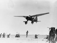 RAF Operations in the Middle East and North Africa, 1939-1943. Westland Lysander Mark II, 'JV-E', of No. 6 Squadron RAF based at Ramleh, Egypt, makes a low-level 'attack' on Australian infantry during an anti-aircraft exercise in the Western Desert.