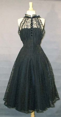 1950's cocktail party dress in fully embroidered black tulle, fitted bodice with high velvet-banded neckline, velvet buttons, wonderfully full skirt, and an attached strapless, boned black taffeta liner. No maker label.