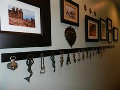 Bottle opener collection hung on a painted strip of wood for display